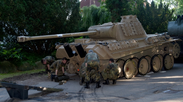 In this July 2, 2015 picture a  World War II -era Panther  tank  is prepared  for transportation from a residential property in Heikendorf,  northern Germany.  Authorities have seized a 45-ton Panther tank, a flak canon and multiple other World War II-era military weapons in a raid on a 78-year-old collector's storage facility in northern Germany. Kiel prosecutor Birgit Hess said the collector is being investigated for possibly violating German weapons laws but his attorney Peter Gramsch told the dpa news agency all the items were properly demilitarized and registered.  (Carsten Rehder/dpa via AP)